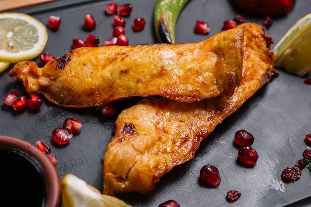 Vooraanzicht gegrilde vis met plakjes granaatappel citroen en narsharab saus