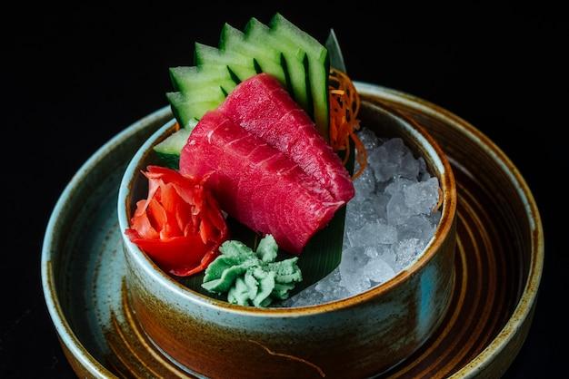 Vooraanzicht gehakte rode gerookte vis met gehakte komkommer wasabi en gember in ijs