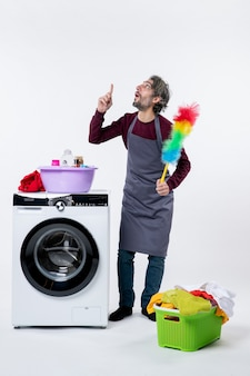 Vooraanzicht geïnteresseerde huishoudster man met stofdoek opzoeken wasmand op witte achtergrond
