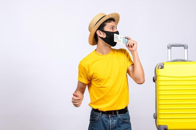 Vooraanzicht geïnteresseerde mannelijke toerist in gele t-shirt die zich dichtbij gele koffer bevindt die reiskaartje steunt