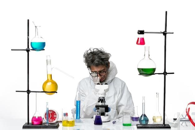Vooraanzicht gekke mannelijke wetenschapper in speciaal beschermend pak aan tafel zitten met oplossingen huilen op witte achtergrond lab ziekte covid science virus