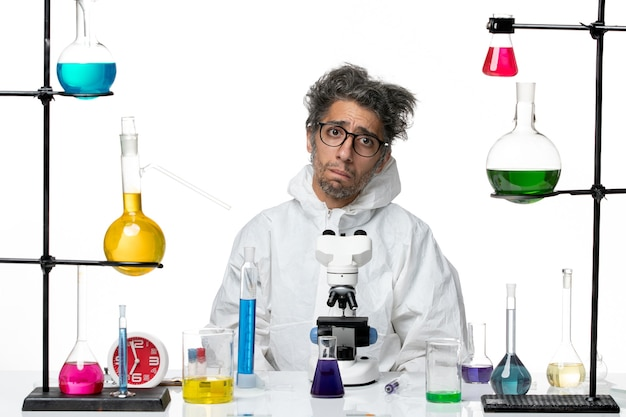 Vooraanzicht gekke mannelijke wetenschapper in speciaal beschermend pak rond de tafel zitten met oplossingen op licht-witte achtergrond ziekte covid lab science virus