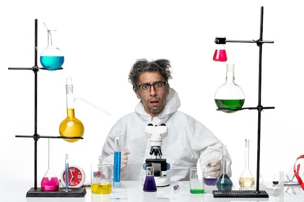 Vooraanzicht gekke mannelijke wetenschapper in speciaal beschermend pak rond de tafel zitten met oplossingen op wit bureau ziekte covid lab wetenschap virus