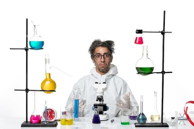 Vooraanzicht gekke mannelijke wetenschapper in speciaal beschermend pak rond de tafel zitten met oplossingen op witte achtergrond lab ziekte covid science virus