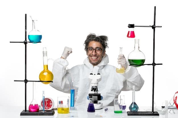 Vooraanzicht gekke mannelijke wetenschapper in speciaal beschermend pak rond de tafel zitten met oplossingen op witte achtergrond ziekte covid lab wetenschap virus