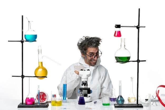 Vooraanzicht gekke mannelijke wetenschapper in speciaal beschermend pak zittend aan tafel met oplossingen lachen op witte achtergrond lab ziekte covid science virus