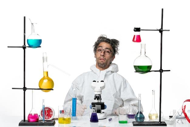 Vooraanzicht gekke mannelijke wetenschapper in speciaal beschermend pak zittend aan tafel met oplossingen op lichte witte achtergrond lab ziekte covid-science virus