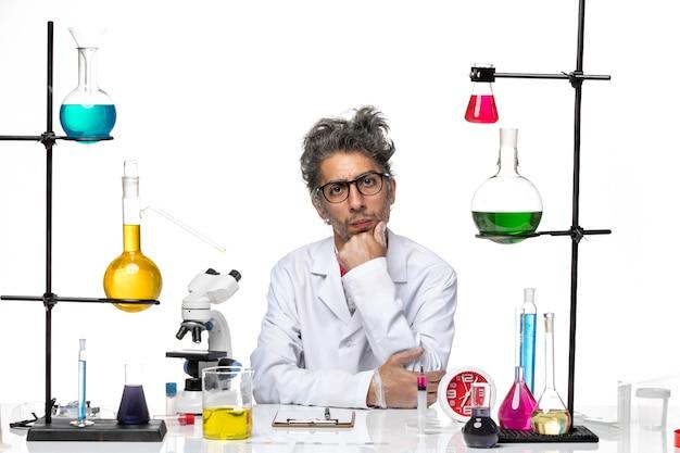 Vooraanzicht gekke wetenschapper in medisch pak rustig zittend op witte achtergrond virus lab chemie covid