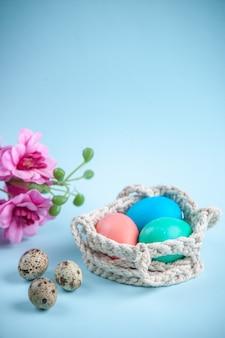 Vooraanzicht gekleurde beschilderde eieren binnen touwen op blauw oppervlak sierlijke kleurrijke lente concept etnische vakantie