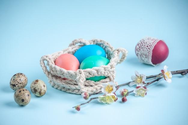 Vooraanzicht gekleurde beschilderde eieren binnen touwen op blauw oppervlak sierlijke lente concept etnische vakantie kleurrijk