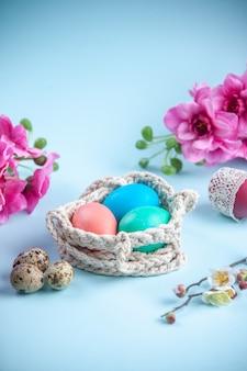 Vooraanzicht gekleurde beschilderde eieren binnen touwen op blauwe ondergrond etnische sierlijke lente concept vakantie kleurrijk