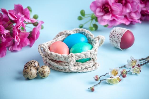 Vooraanzicht gekleurde beschilderde eieren binnen touwen op blauwe ondergrond etnische sierlijke voorjaarsvakantie kleurrijk