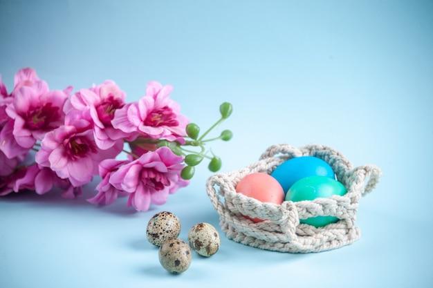 Vooraanzicht gekleurde beschilderde eieren binnen touwen op blauwe ondergrond kleurrijke lente concept etnische sierlijke feestdagen