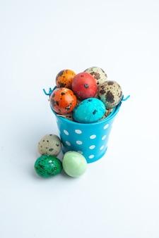Vooraanzicht gekleurde beschilderde eieren in blauwe mand op witte achtergrond sierlijke lente concept novruz horizontale vakantie