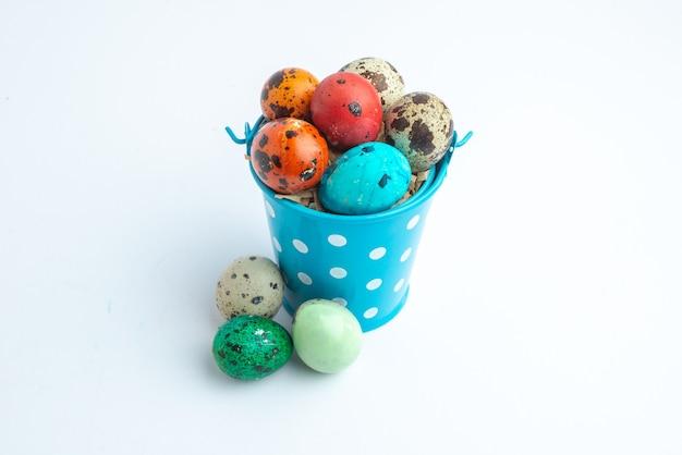 Vooraanzicht gekleurde beschilderde eieren in blauwe mand op witte achtergrond sierlijke lente kleurrijke concept novruz horizontale vakantie