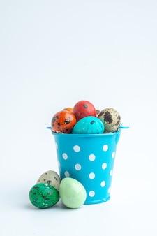 Vooraanzicht gekleurde beschilderde eieren in blauwe mand op witte achtergrond sierlijke lente kleurrijke concept vakantie novruz horizontal
