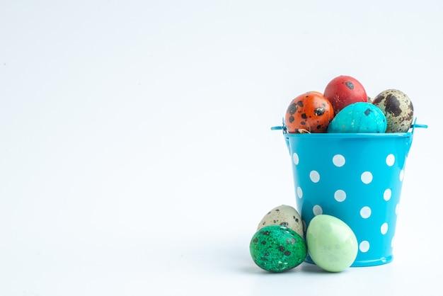 Vooraanzicht gekleurde beschilderde eieren in blauwe mand op witte achtergrond sierlijke lente kleurrijke vakantie novruz horizontal