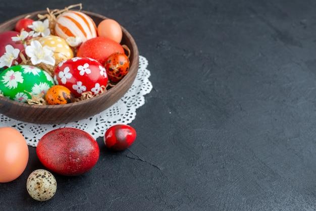 Vooraanzicht gekleurde ontworpen eieren binnen bruine plaat donkere achtergrond vakantie kleurrijke novruz sierlijke lente