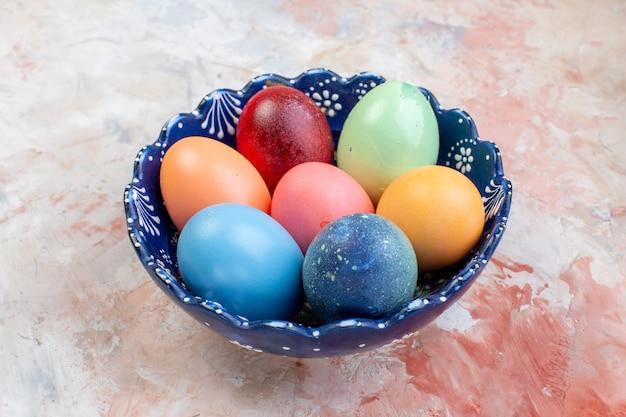Vooraanzicht gekleurde paaseieren binnen blauwe plaat op lichte achtergrond sierlijke vakantie horizontale kleurrijke lente pasen