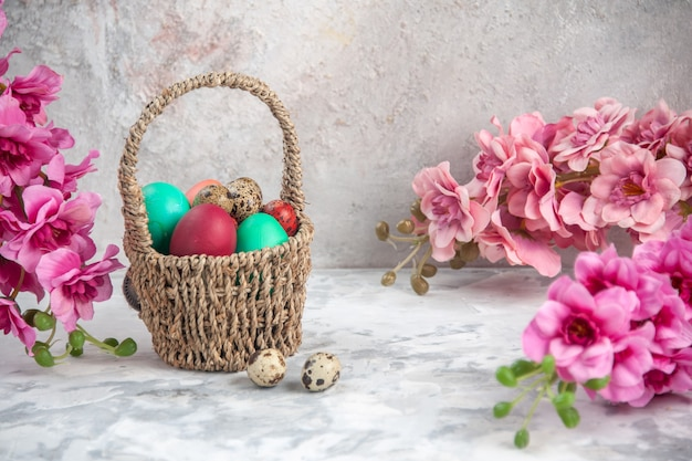 Vooraanzicht gekleurde paaseieren binnen ontworpen mand met bloemen op witte achtergrond sierlijke concept kleurrijke lente novruz vrouwelijkheid
