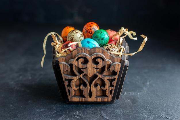Vooraanzicht gekleurde paaseieren in elegant ontworpen doos donkere achtergrond sierlijke kleurrijke etnische kleur vakantie pasen