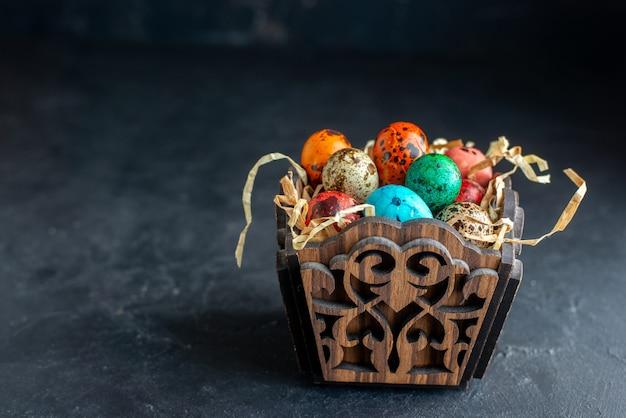 Vooraanzicht gekleurde paaseieren in elegant ontworpen doos donkere achtergrond sierlijke kleurrijke etnische kleuren vakantie pasen