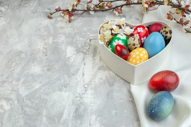 Vooraanzicht gekleurde paaseieren in hartvormige doos op witte achtergrond kleurrijke vrouwelijkheid pasen concept lente sierlijke novruz