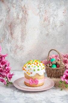 Vooraanzicht gekleurde paaseieren in ontworpen mand met bloemen en cake op wit oppervlak
