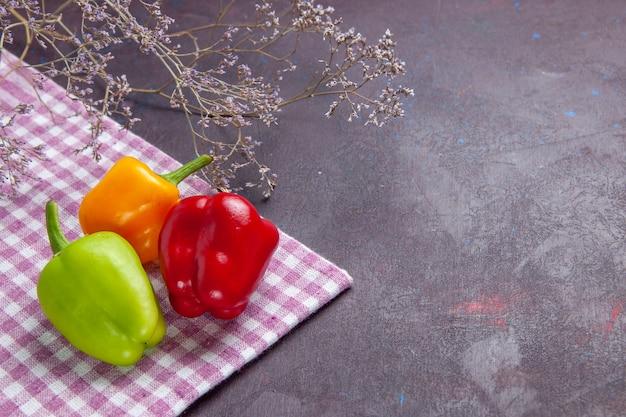 Vooraanzicht gekleurde paprika's verse op grijs oppervlak plantaardige peper pittig warm eten