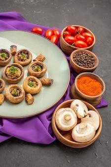 Vooraanzicht gekookte champignons in bord met kruiden op paarse tissueschotel maaltijd paddestoel diner koken
