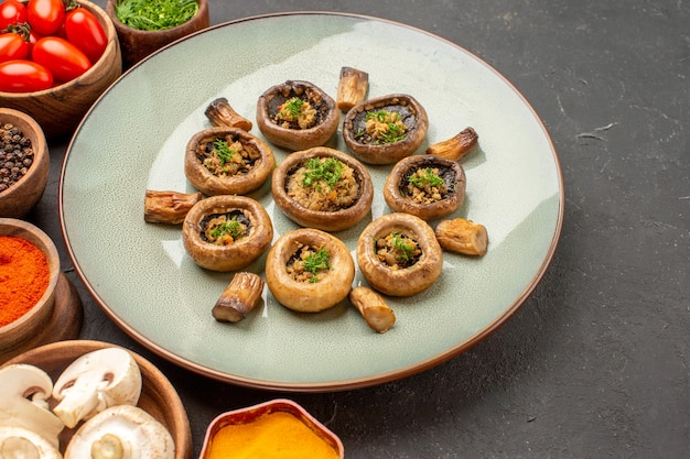 Vooraanzicht gekookte champignons met tomaten en kruiden op een donkere achtergrond schotel maaltijd koken champignons diner