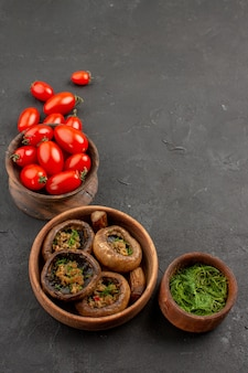 Vooraanzicht gekookte champignons met tomaten op donkere tafel champignons wilde pasta