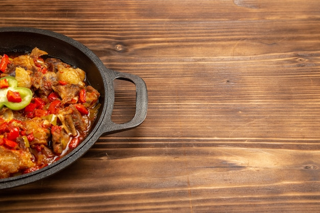 Vooraanzicht gekookte groentemaaltijd in pan op het bruine houten oppervlak