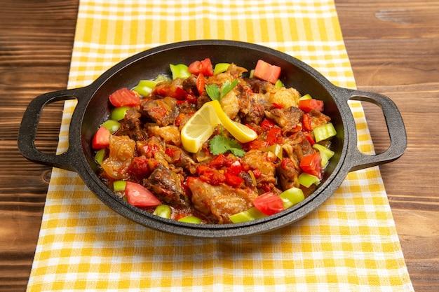 Vooraanzicht gekookte groentemaaltijd met vlees en gesneden groene paprika's op bruin bureau