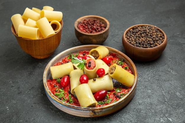 Vooraanzicht gekookte italiaanse pasta heerlijke maaltijd met tomatensaus en kruiden op grijze achtergrond deeg pasta vlees eten saus