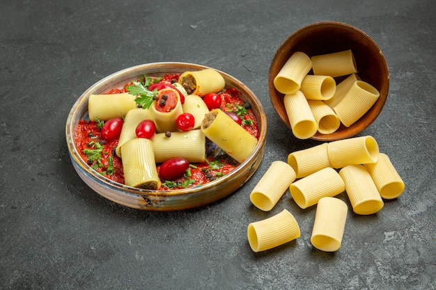 Vooraanzicht gekookte italiaanse pasta heerlijke maaltijd met tomatensaus op grijze achtergrond deeg pasta vlees eten saus