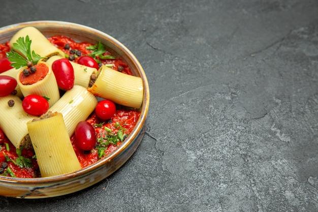 Vooraanzicht gekookte italiaanse pasta heerlijke maaltijd met vlees en tomatensaus op het grijze achtergrond deeg pasta vlees saus eten