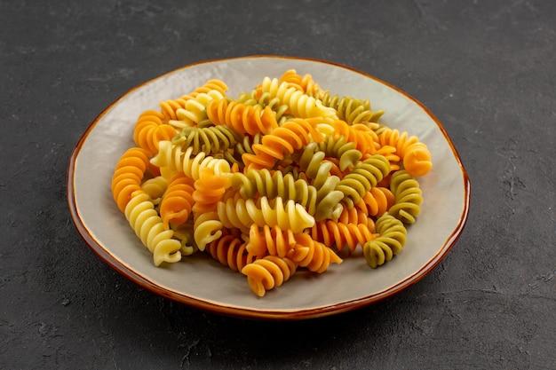 Vooraanzicht gekookte italiaanse pasta ongebruikelijke spiraal pasta binnen plaat op de donkere ruimte