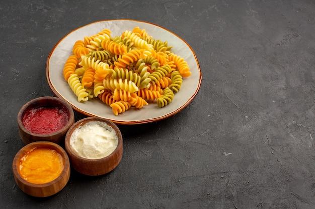 Vooraanzicht gekookte italiaanse pasta ongebruikelijke spiraalpasta met kruiden op donkere ruimte