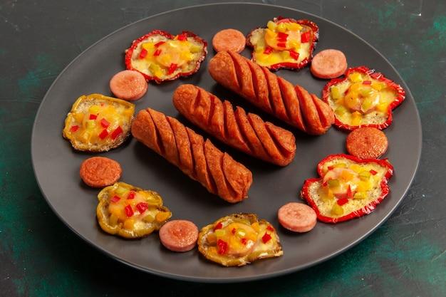 Vooraanzicht gekookte paprika met worst binnen plaat op donkere ondergrond