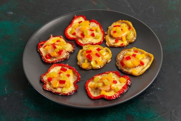 Vooraanzicht gekookte paprika's voor lunch in plaat op donkere ondergrond