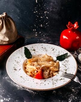 Vooraanzicht gekookte pasta lekker binnen witte plaat op de grijze vloer