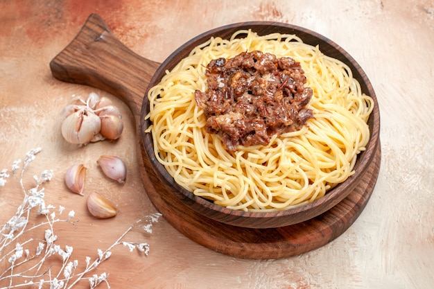 Vooraanzicht gekookte spaghetti met gehakt op houten bureau pastadeegschotel kruiden