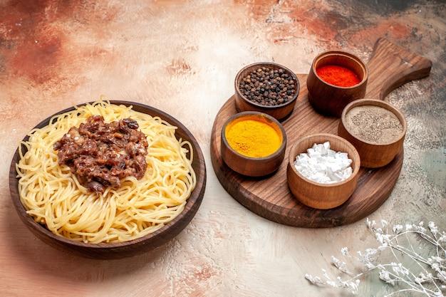 Vooraanzicht gekookte spaghetti met gehakt op lichte tafel pasta vlees deeg schotel maaltijd