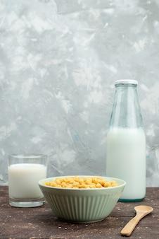 Vooraanzicht gele granen binnen plaat met verse koude melk op wit, ontbijt cornflakes granen voedsel