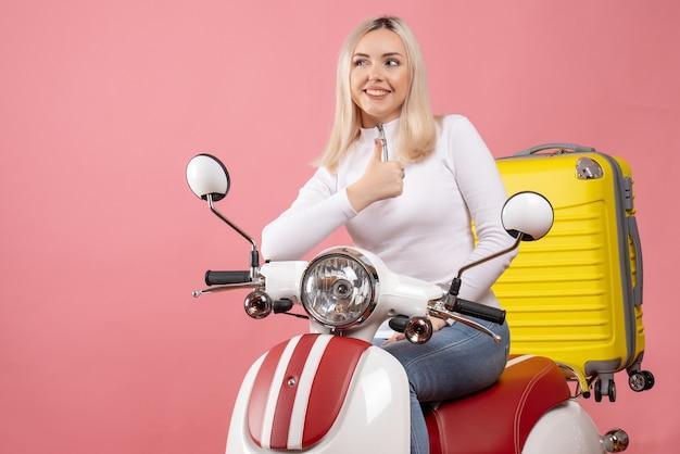 Vooraanzicht gelukkig blond meisje op bromfiets duimen opgevend