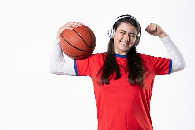Vooraanzicht gelukkig jong wijfje in sportkleren met basketbal