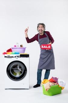 Vooraanzicht gelukkig mannetje in schort dat verkoopteken omhoog houdt dat dichtbij wasmachine op witte achtergrond staat