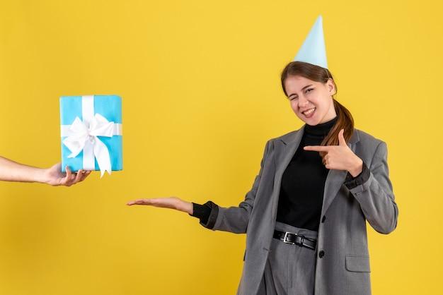 Vooraanzicht gelukkig schattig meisje met feestmuts kerstcadeaus ontvangen