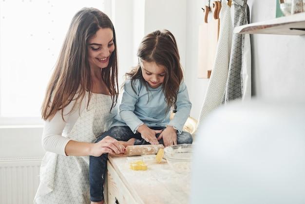 Vooraanzicht. gelukkige dochter en moeder bereiden samen bakkerijproducten. kleine helper in de keuken.
